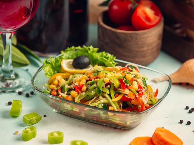 Insalata di verdure con peperoni, cetrioli, mais e sesamo