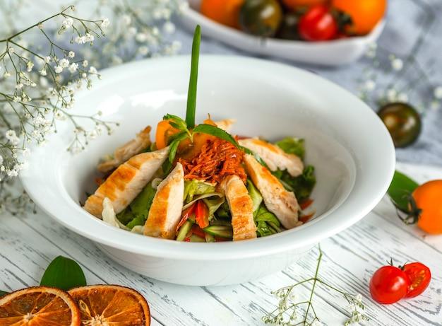 Insalata di verdure con pollo e cipolle fritte e carote grattugiate