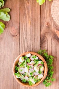 Insalata di verdure della primavera in un piatto di legno