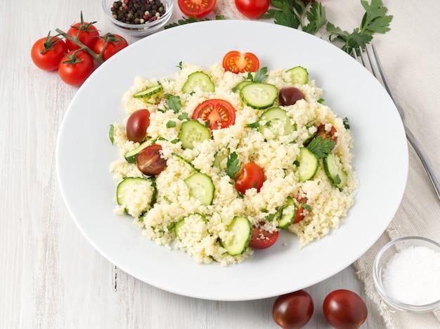 Insalata di verdure fresca con couscous, pomodori, cetrioli, prezzemolo,