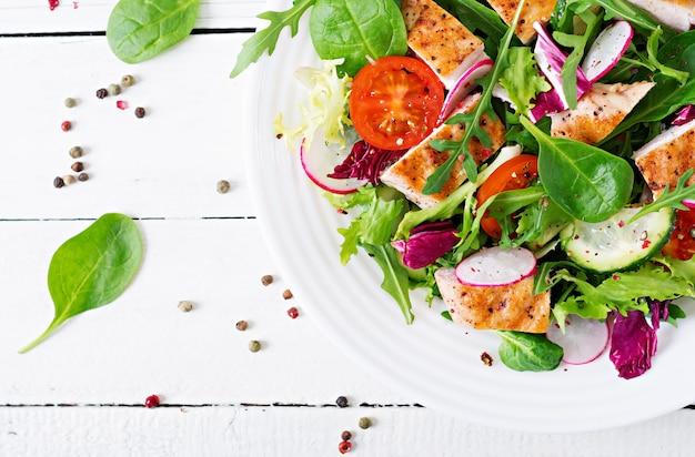 Insalata di verdure fresche con petto di pollo grigliato - pomodori, cetrioli, ravanello e foglie di lattuga mista. insalata di pollo. cibo salutare. vista dall'alto
