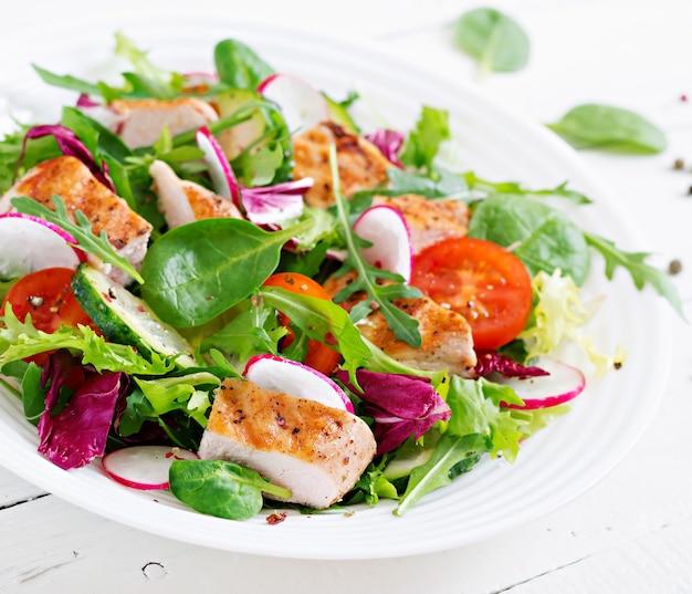 Insalata di verdure fresche con petto di pollo grigliato - pomodori, cetrioli, ravanello e foglie di lattuga mista. insalata di pollo. cibo salutare.