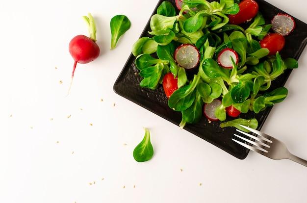 Insalata di verdure fresche di ravanello, pomodori e insalata di mais o valerianella locusta.