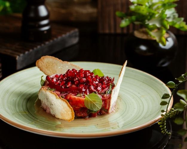 Insalata di verdure fresche guarnita con melograni, basilico e croste di pane