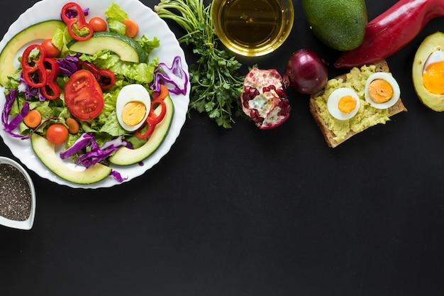 Insalata di verdure fresche; pane tostato; frutta; olio su sfondo nero