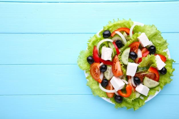 Insalata di verdure fresche su fondo di legno blu