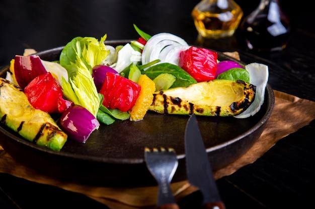 Insalata di verdure grigliata calda deliziosa con avocado in ristorante. sano cibo esclusivo sul grande primo piano piatto nero