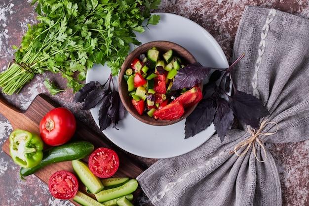 Insalata di verdure in una tazza di legno servita con erbe aromatiche, vista dall'alto