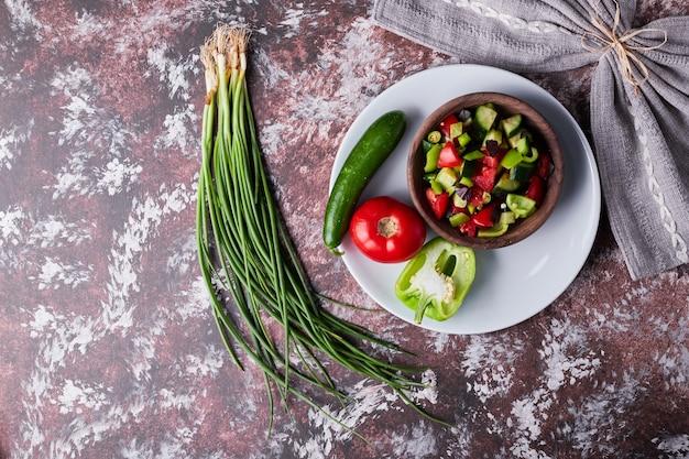 Insalata di verdure in una tazza di legno sul marmo.