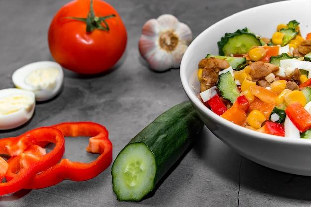 Insalata di verdure luminosa con pollo su uno sfondo di cemento grigio. preparare una deliziosa insalata per una dieta sana.