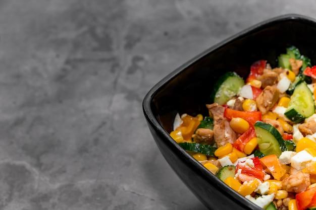 Insalata di verdure luminosa con pollo su uno sfondo di cemento grigio.