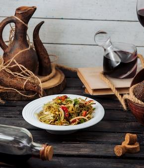 Insalata di verdure mista all'interno del piatto bianco su un tavolo rustico.