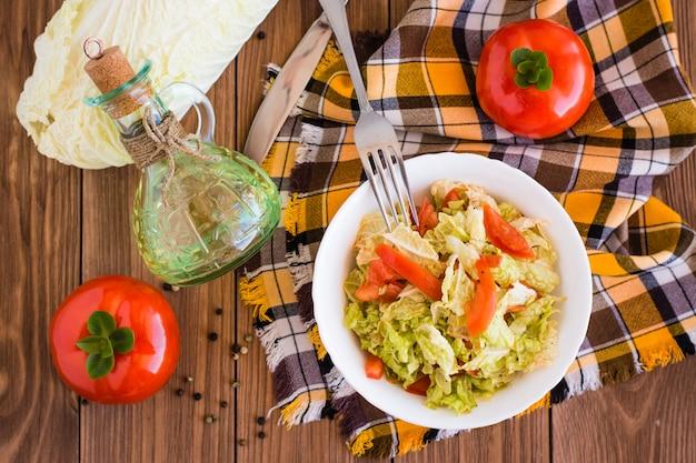 Insalata di verdure pronta da mangiare, pomodori e cavolo cinese su una tavola di legno, vista superiore