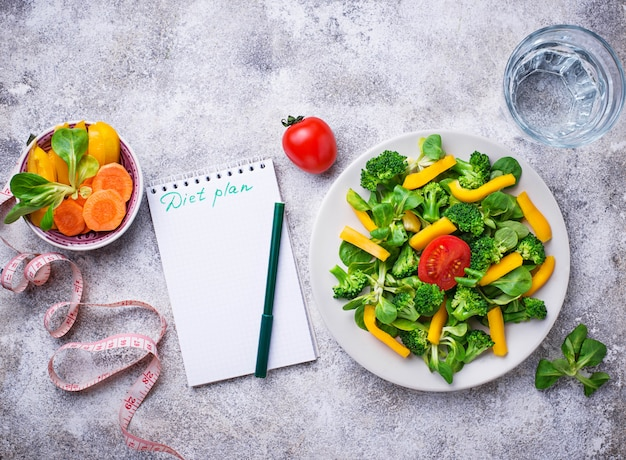 Insalata di verdure sana, acqua e nastro di misurazione