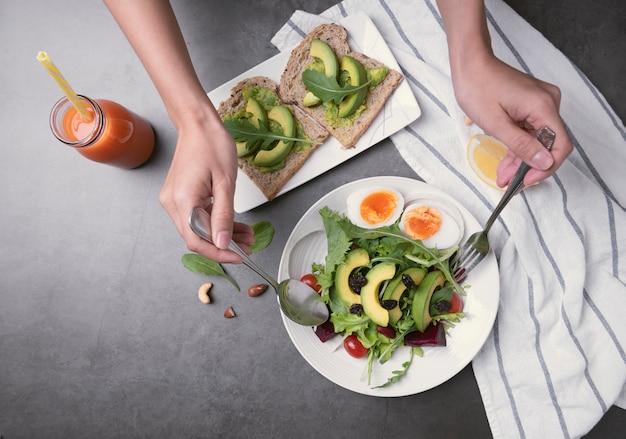 Insalata di verdure sana fresca con uovo, pomodoro, avocado, spinaci, lattuga nel piatto sul tavolo.