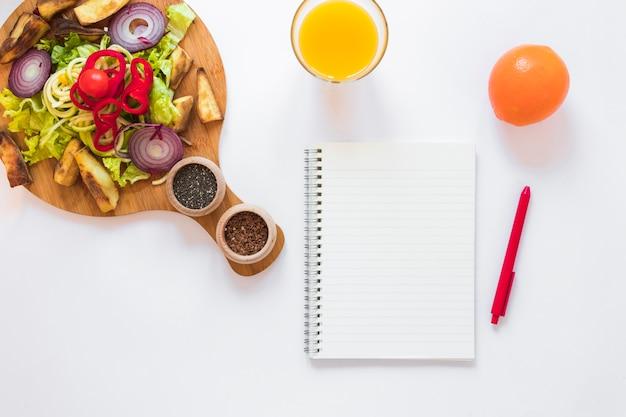 Insalata di verdure sane; succo; frutta; blocco note in bianco e penna su sfondo bianco