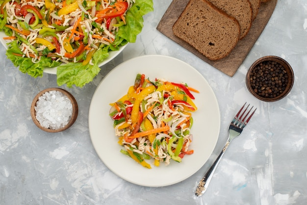 Insalata di verdure saporita di vista superiore con verdure affettate e insalata verde con pagnotte di pane su grigio, pasto di insalata di verdure