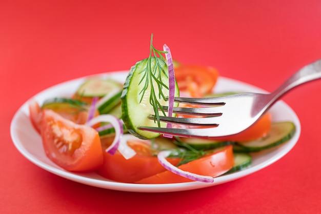 Insalata di verdure semplice di pomodori, cetrioli, cipolle e aneto nel piatto bianco su sfondo rosso brillante.