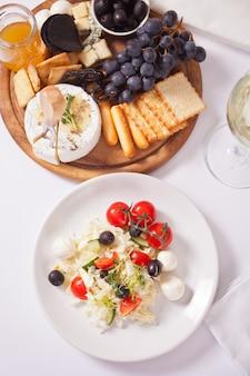 Insalata di verdure sul piatto, bicchiere di vino bianco e piatto con formaggi assortiti, frutta e altri snack.