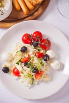 Insalata di verdure sul piatto e piatto con formaggi assortiti, frutta e altri spuntini.