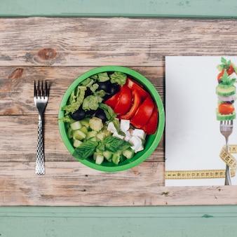 Insalata di verdure verde stagionale con erbe e pomodoro.