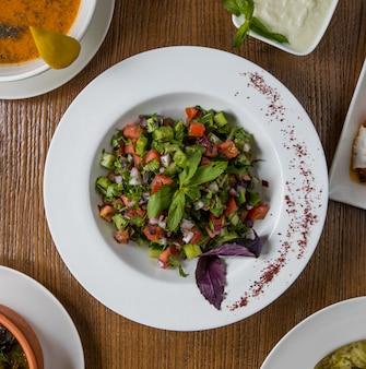 Insalata di verdure verdi vista dall'alto con cubi all'interno del piatto bianco.