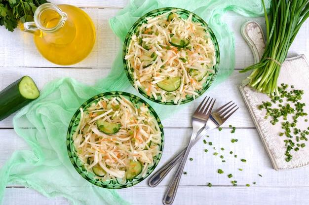 Insalata dietetica con cavolo, cetriolo, carota, verdure. insalata succosa della molla dagli ortaggi freschi su un fondo di legno bianco. nutrizione appropriata. la vista dall'alto