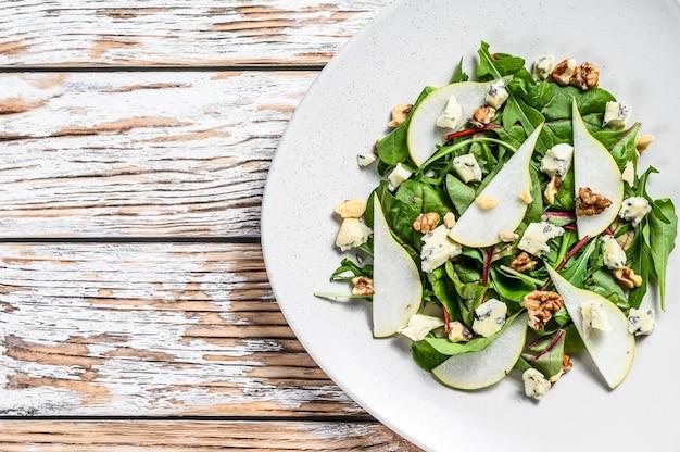 Insalata dietetica con gorgonzola blu, pere, noci, bietola e rucola. sfondo bianco. vista dall'alto. copia spazio