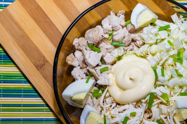 Insalata dietetica per una corretta alimentazione con pollo e uova su una stuoia verde.
