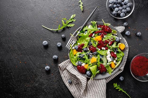 Insalata estiva con foglie di insalata, frutta, bacche e formaggio