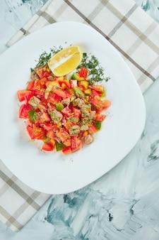 Insalata estiva fatta in casa con pomodori, olio d'oliva e vitello al forno su un piatto bianco su un tavolo grigio.