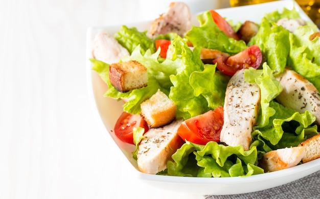 Insalata fresca a base di pomodoro, rucola, petto di pollo, uova, rucola, cracker e spezie. insalata di caesar in una ciotola bianca e trasparente su fondo di legno