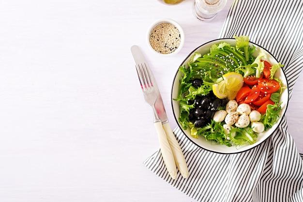 Insalata fresca con avocado, pomodoro, olive e mozzarella in una ciotola.
