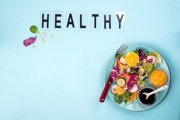 Insalata fresca con frutta e verdura su sfondo blu