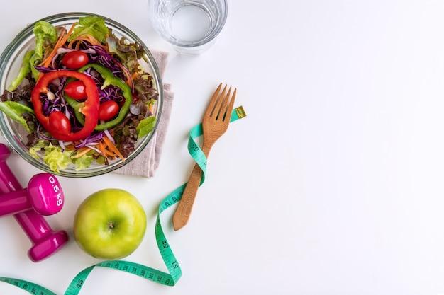 Insalata fresca con mela verde, manubri e nastro di misurazione su sfondo bianco.