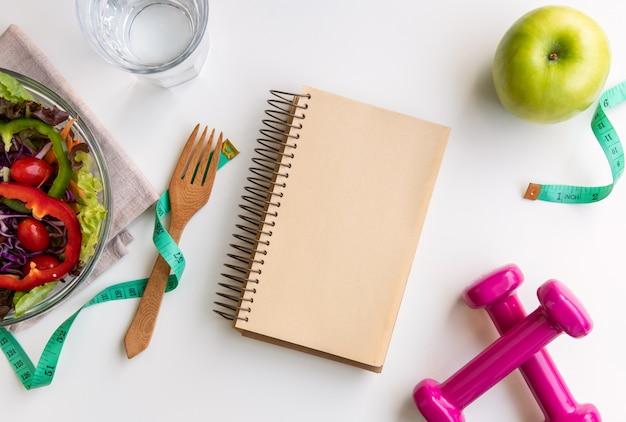 Insalata fresca con notebook, mela verde, manubri e nastro di misurazione su sfondo bianco.