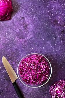 Insalata fresca di cavolo rosso in una ciotola di vetro su uno sfondo viola scuro. cibo vegetariano sano. vista dall'alto, copia spazio