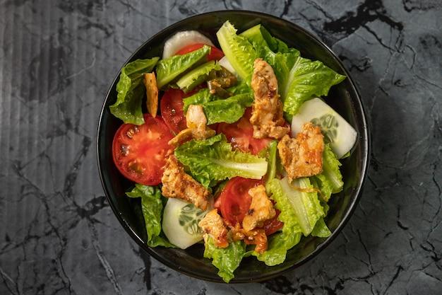 Insalata fresca di lattuga romana e pomodori con pollo arrosto