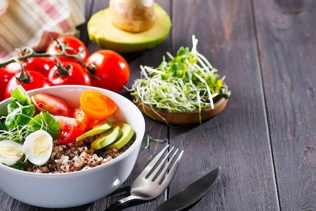 Insalata fresca e sana con quinoa, pomodorini e verdure miste, avocado, uova e micro verdure su legno