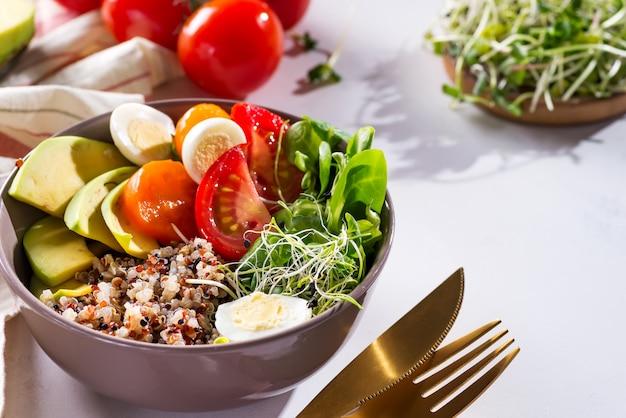 Insalata fresca e sana con quinoa, pomodorini e verdure miste, avocado, uova e micro verdure su marmo