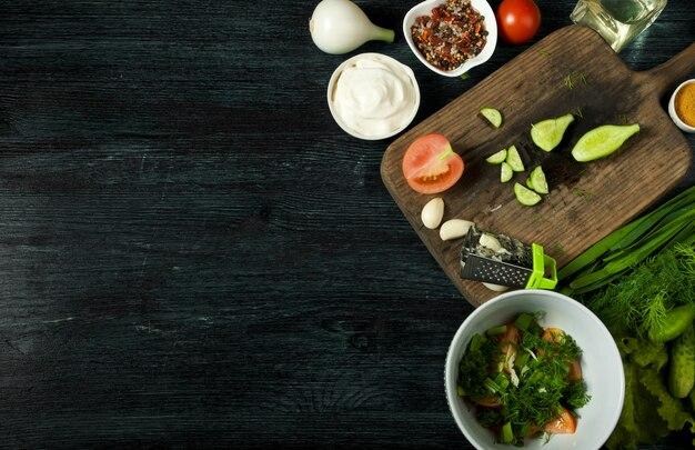 Insalata fresca in un piatto su una superficie scura. aglio, pomodoro, cetriolo, aneto e cipolla in un piatto di superficie scura.