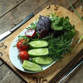 Insalata fresca superiore con cetrioli pomodori ed erbe sul piatto su legno