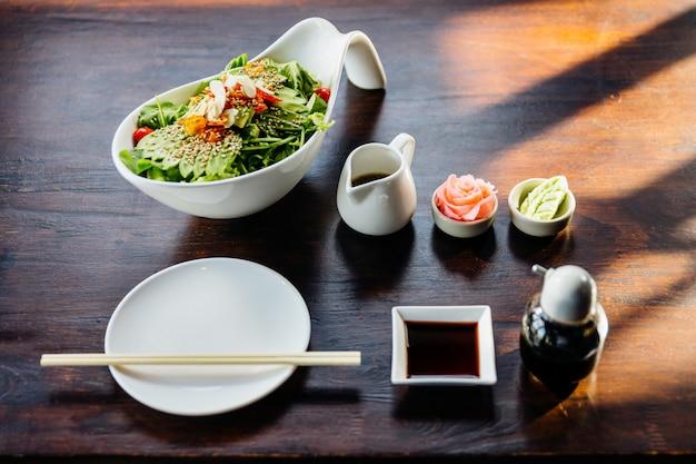 Insalata giapponese con condimento per insalata di sesamo condita con avocado, pomodoro, quercia verde, mandorle e sesamo. servito con zenzero sottaceto e wasabi.