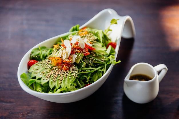 Insalata giapponese con condimento per insalata di sesamo condita con avocado, pomodoro, quercia verde, mandorle e sesamo.
