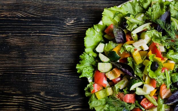 Insalata greca con cetrioli freschi, pomodori, peperoni dolci, lattuga, cipolle rosse, formaggio feta e olive con olio d'oliva su una superficie scura