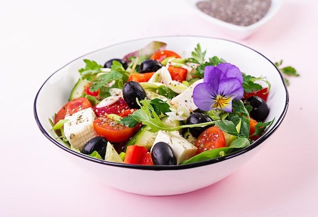 Insalata greca con cetrioli, pomodori, peperoni, lattuga, cipolla verde, formaggio feta e olive con olio d'oliva
