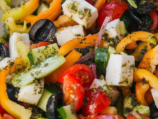Insalata greca con pomodori, cetrioli, peperoni, formaggio feta, olive e cipolle