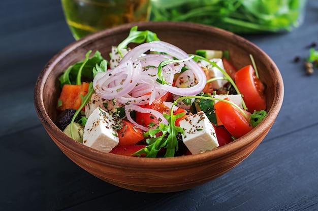 Insalata greca con pomodoro fresco, cetriolo, cipolla rossa, basilico, formaggio feta, olive nere e erbe italiane