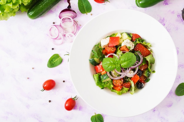Insalata greca con pomodoro fresco, cetriolo, cipolla rossa, basilico, lattuga, formaggio feta, olive nere ed erbe italiane. vista dall'alto