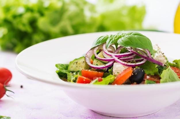 Insalata greca con pomodoro fresco, cetriolo, cipolla rossa, basilico, lattuga, formaggio feta, olive nere ed erbe italiane
